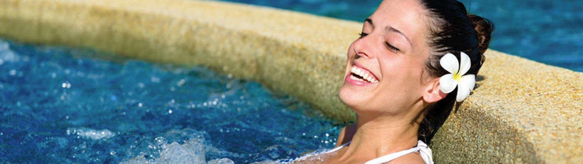 lachende Frau im Whirlpool mit kristallklarem Wasser